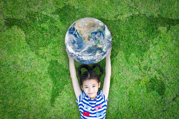earth day, ecological friendly and corporate social responsibility concept with kid raising world on green lawn: element of the image furnished by nasa - earth day stock pictures, royalty-free photos & images