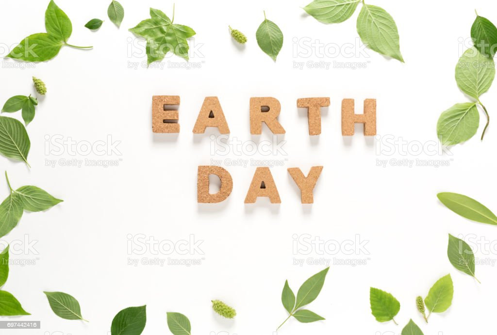 Earth Day text with green leaves top view stock photo