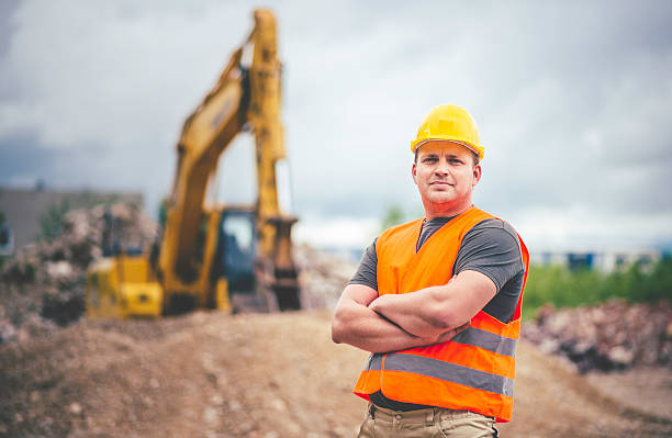 earth digger driver at construction site - builders stock photos and pictures