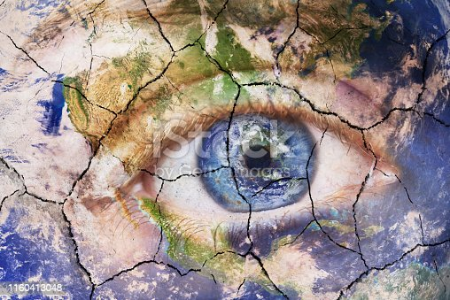 Earth extinction concept. Close up image of woman face with earth painted cracked texture with iris earth. Creative composite of macro Eye with Earth as Iris. Elements of this image furnished by NASA.