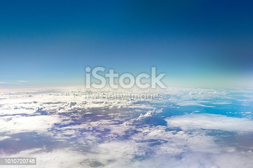 A picture of clouds over an ocean taken from the window of an aircraft.