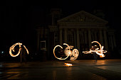 Sofia, Bulgaria - March 19, 2016: Performers are spinning torches while performing a fire show at night celebrating the international Earth hour event in Sofia, Bulgaria. Long exposure.