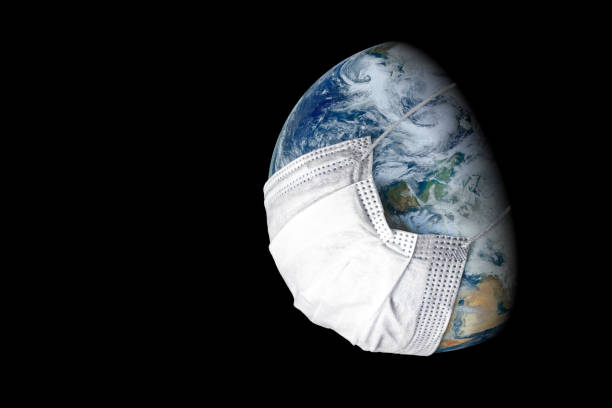 Earth in medical mask isolated on black background, concept of coronavirus in world and COVID-19 pandemic. Globe with protect from corona virus. stock photo