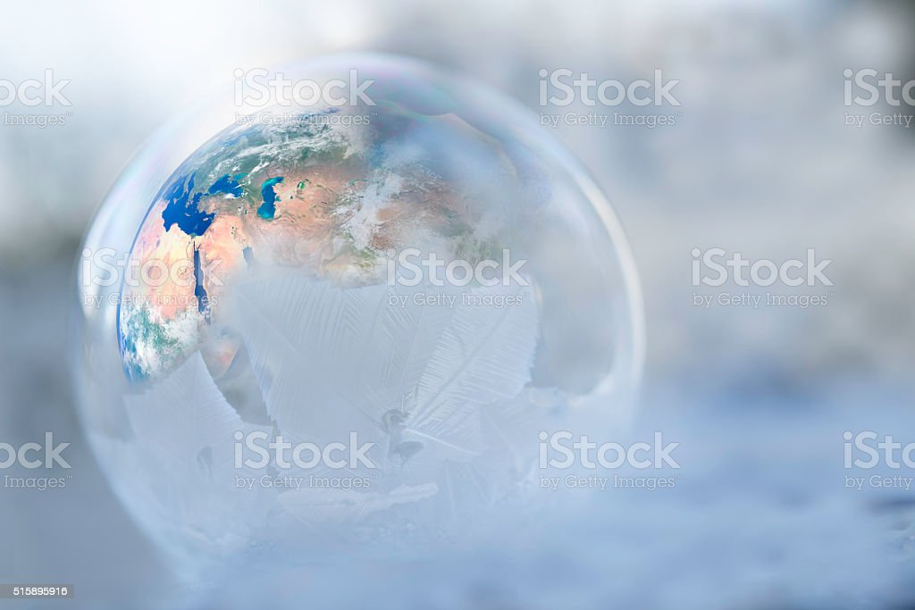 Earth inside a half frozen globe for showing weather change stock photo