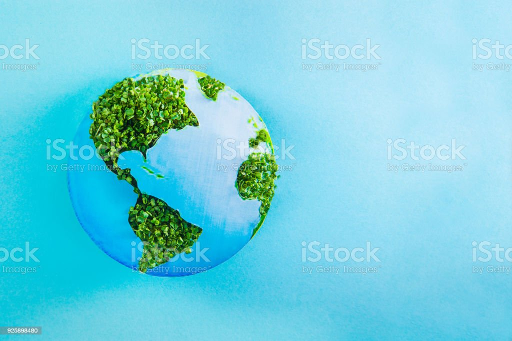Earth model made of paper and fresh green sprouts collage on blue background. Green planet creative concept. Earth day. Selective focus, space for text. stock photo