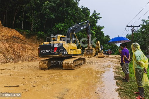 Ko Lanta, Thailand - July 19 2019: Torrential rain during Monsoon season has caused a landslide onto the road. Several bulldozers are moving the dirt to clear the roadblock. Recent deforestation has removed the trees that would normally absorb this rainwater and prevent the disaster. Several onlookers are watching in the rain.