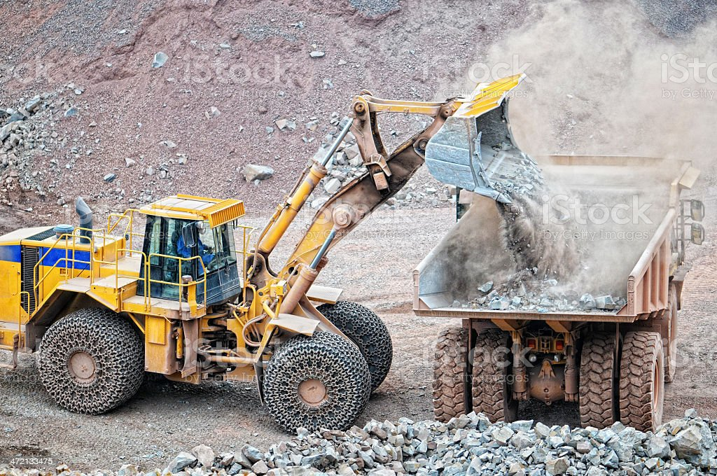 earth mover loading a dumper truck surface mine royalty-free stock photo