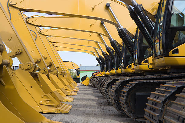 Earth Movers row of excavators construction machinery stock pictures, royalty-free photos & images