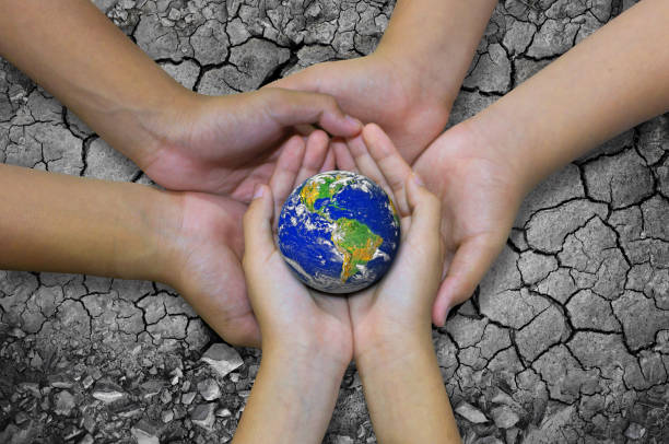 Earth planet in asian Children hand isolated on Ground arid barren stock photo