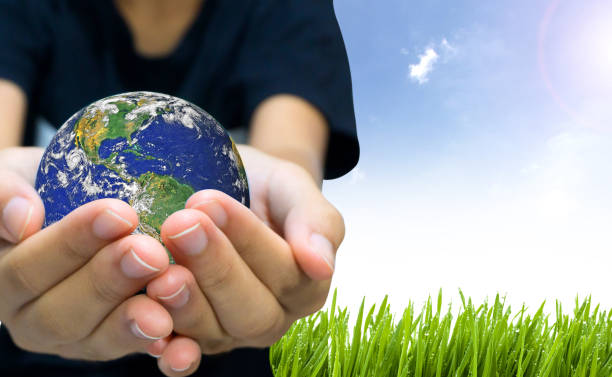 Earth planet the hand on nature and blue sky background stock photo