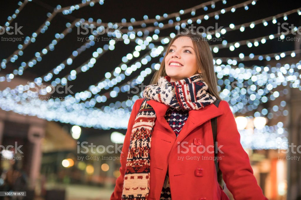 Beautiful young woman walking the city streets illuminated by the...