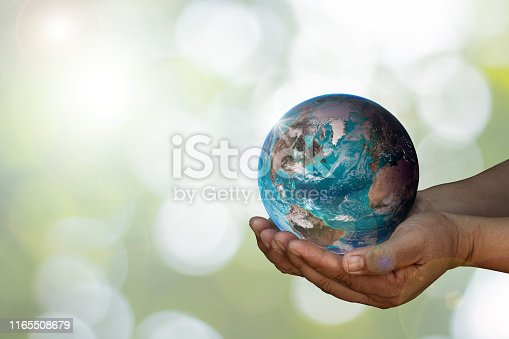 Earth was holding in human hands on blurred. World environment day and green earth. Energy saving environment nature conservation concept with space for text.