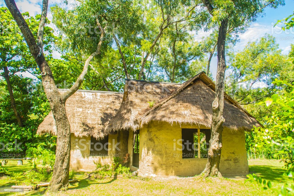 Earthen house under shade of trees. An earth house, also known as earth berm, earth sheltered home, or eco-house is an architectural style by use the natural terrain to help form the walls of a house. royalty-free stock photo