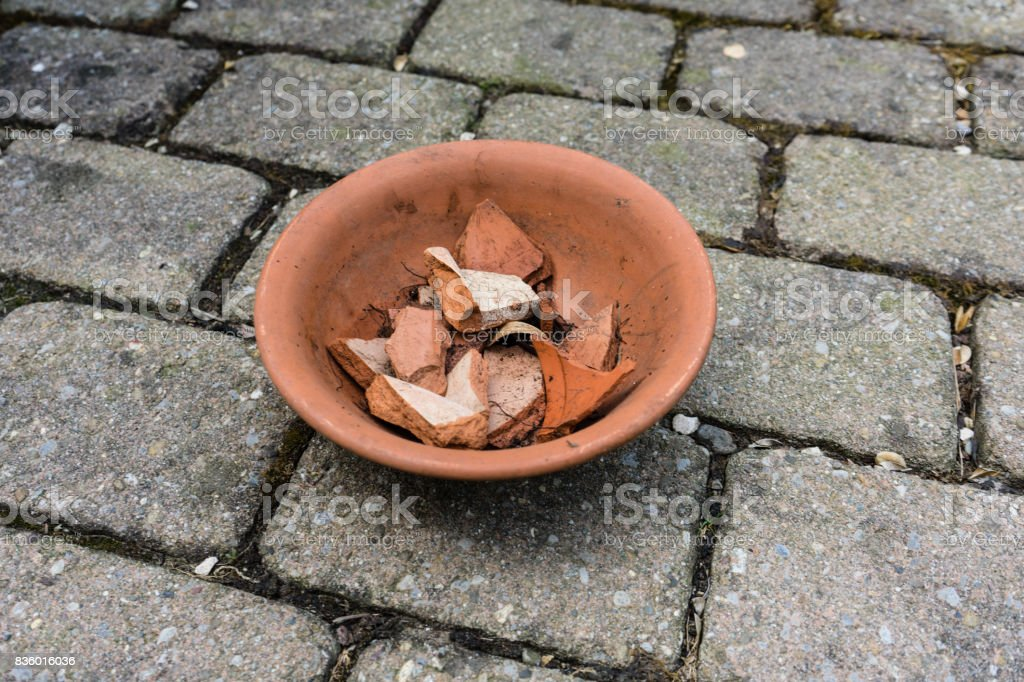 earthenware flower pot with cracked pieces inside stock photo
