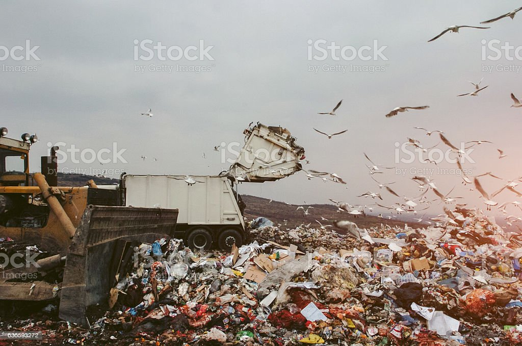 Earthmover and garbage truck on a landfill stock photo