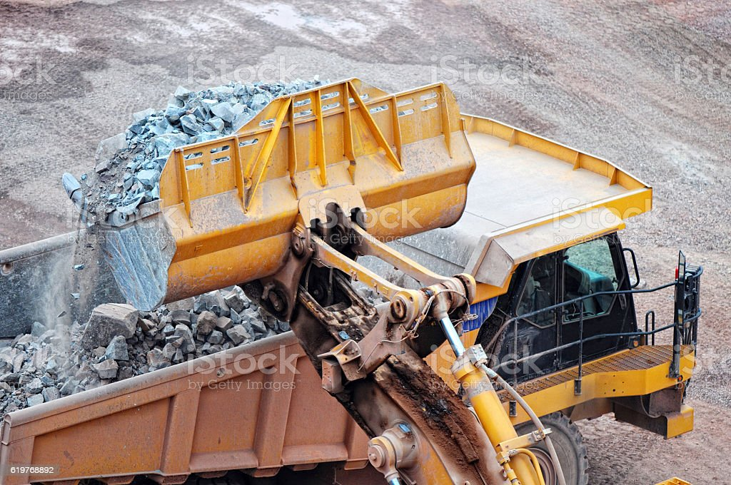 earthmover loading a dumper truck with stone material stock photo