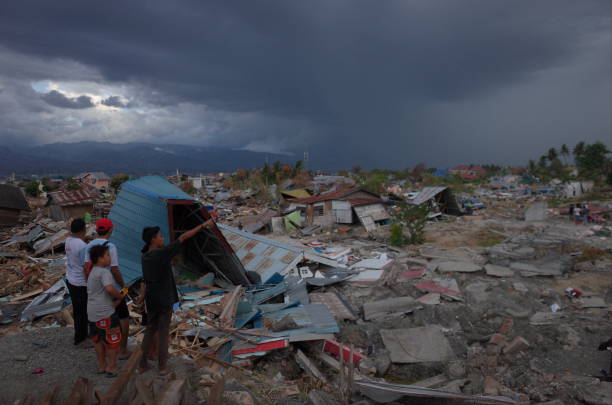 Earthquarke and Tsunami in Indonesia PALU, INDONESIA - OCTOBER 11th, 2018: Victims of the earthquake and tsunami in the National Housing Agency of Balaroa scavenge the remains of their ruins on October 11th, 2018 in Palu, Indonesia. A tsunami triggered by a magnitude 7.5 earthquake slammed into Indonesia's coastline on the island of Sulawesi as people are increasingly growing desperate for food, fuel, and water, while emergency services fear that survivors may still be trapped under the rubble. sulawesi stock pictures, royalty-free photos & images