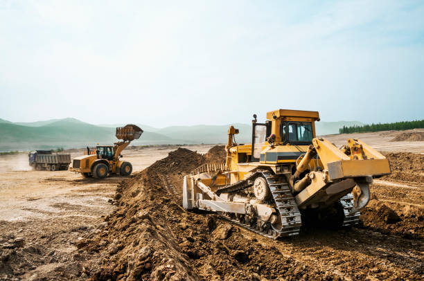 Earthwork, working machinery on a summer day Earthwork, working machinery on a summer day construction machinery stock pictures, royalty-free photos & images