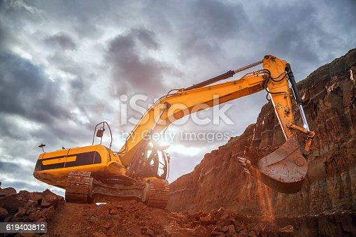 Excavator digging in red soil