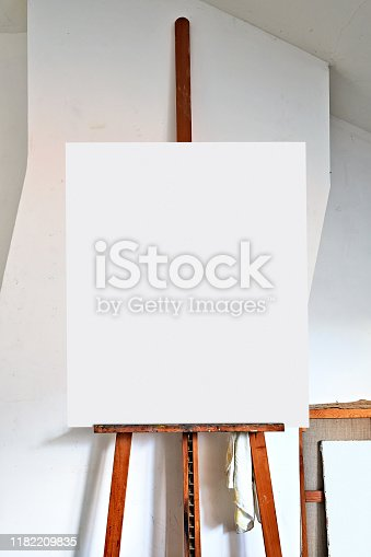 671393252 istock photo easel and empty canvas in an artist's studio 1182209835