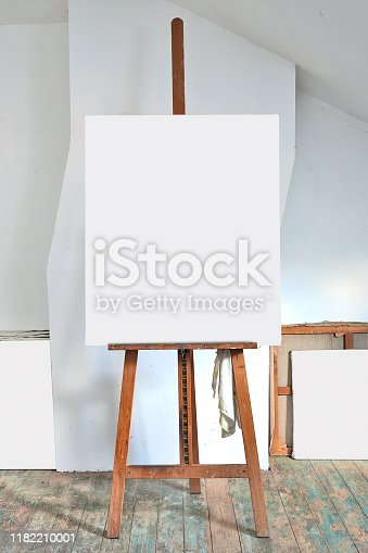 671393252 istock photo easel and empty canvas in an artist's studio 1182210001