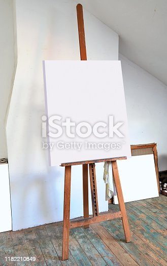 671393252 istock photo easel and empty canvas in an artist's studio 1182210849