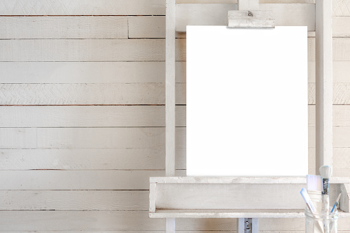 istock Easel with blank canvas for poster with shiplap 1131717814
