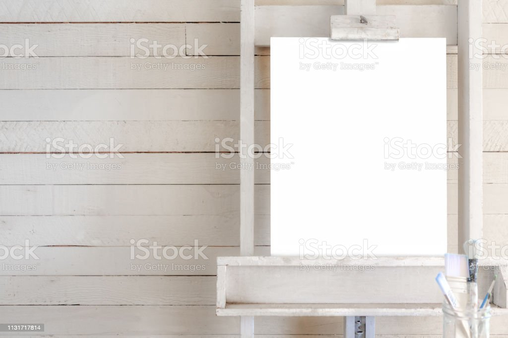 Easel with blank canvas for poster with shiplap stock photo