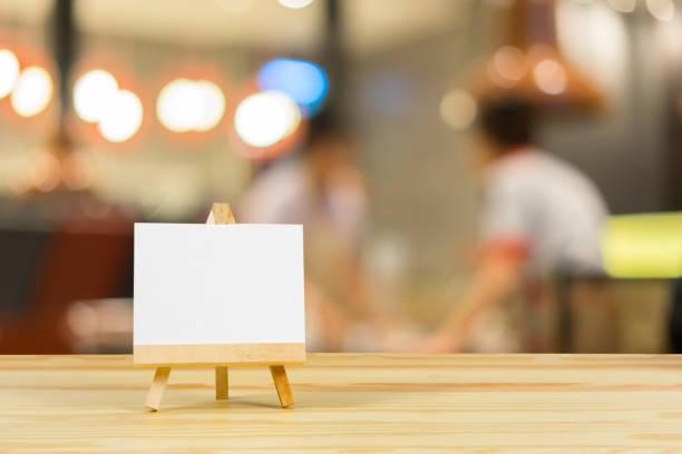 Staffelei mit leeren Leinwand auf Holztisch, Billboard auf Holz Tischplatte mit mitgelieferten Bokeh Hintergrund, Vorlage mock für Montage der Anzeige Ihre product.vintage Farbe – Foto