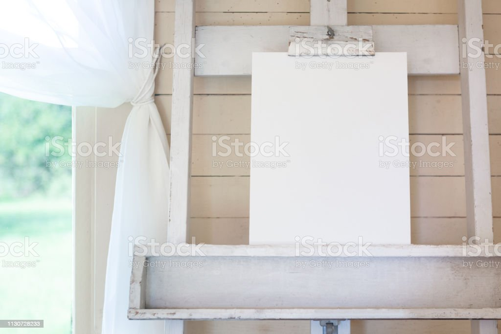 Easel with blank canvas, shiplap, next to window with curtains stock photo