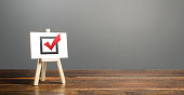 Easel with red voting tick. Checkbox. Democratic elections, referendum. Right to choose, change of power. Checklist verification, self-discipline. Necessary quality criteria, skills, approval symbol