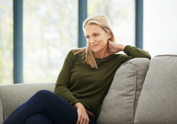 Easing in to a calm and relaxing weekend Shot of a mature woman relaxing on the sofa at home one mature woman only stock pictures, royalty-free photos & images