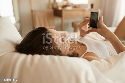 Shot of a young woman lying in bed and taking pictures on her smartphone in the morning