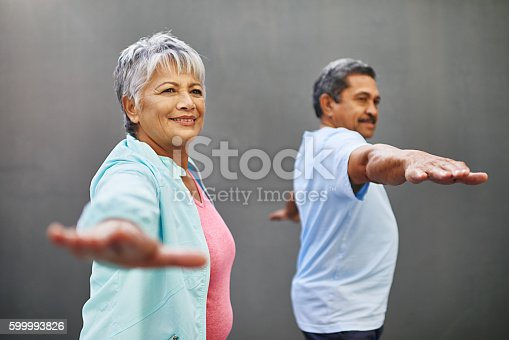 Shot of a happy older couple practicing yoga together outdoors against a gray background