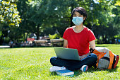 East asian male student with face mask at campus of university in summer