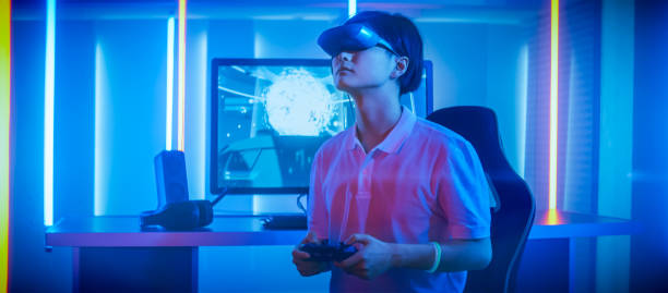 east asian pro gamer wearing virtual reality headset plays online video game shooter using joysticks / controllers as swords. cool retro neon colors in the room. - esports stock photos and pictures