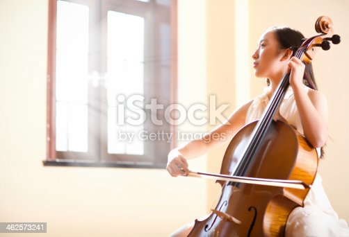 East asian teenage girl playing cello indoor,sunlight shining from the window
