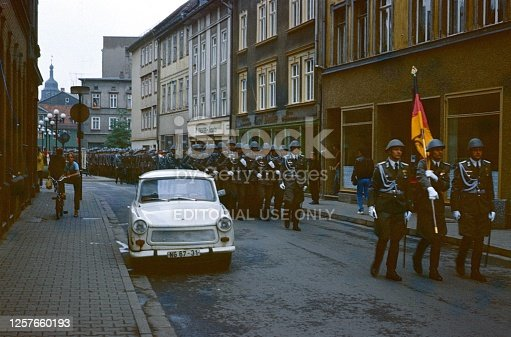 Thuringia (exact location unfortunately not known), German Democratic Republic, 1978. East German military after swearing in of recruits marches through a small town back to the barracks. Also: spectators, buildings and a Trabant (car).