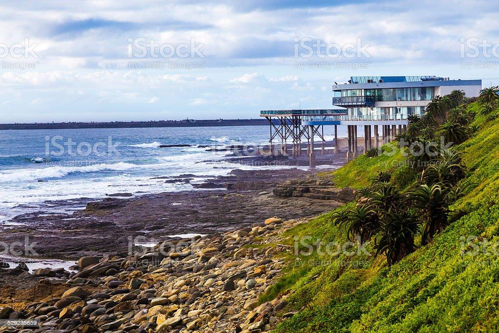 East London beachfront restaurant on rocky shores stock photo