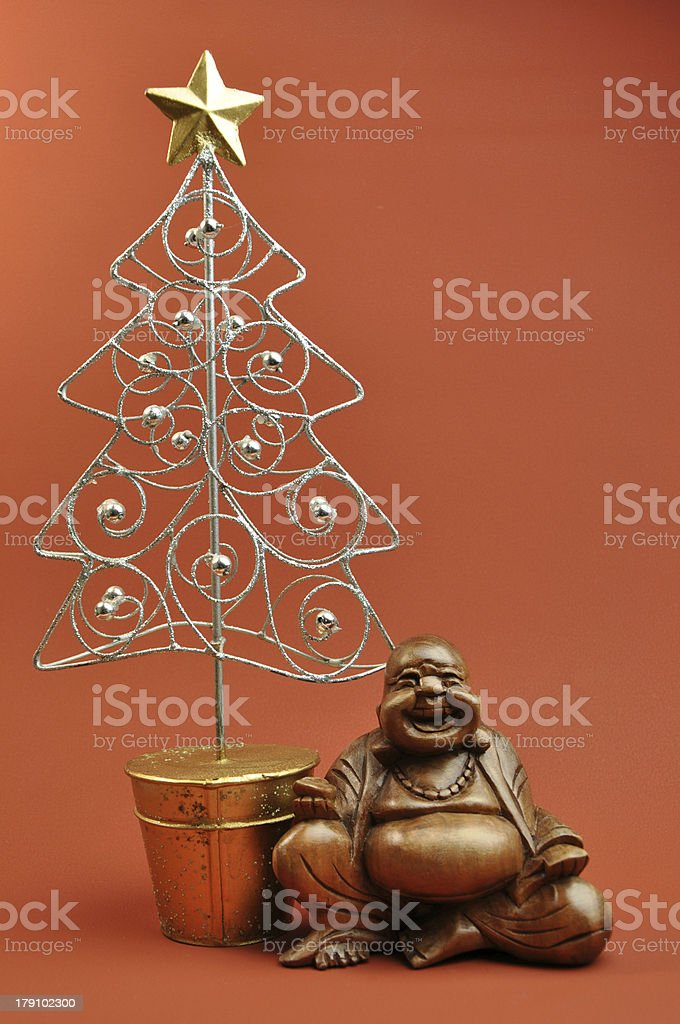 East Meets West Buddha sitting next to a Christmas Tree royalty-free stock photo