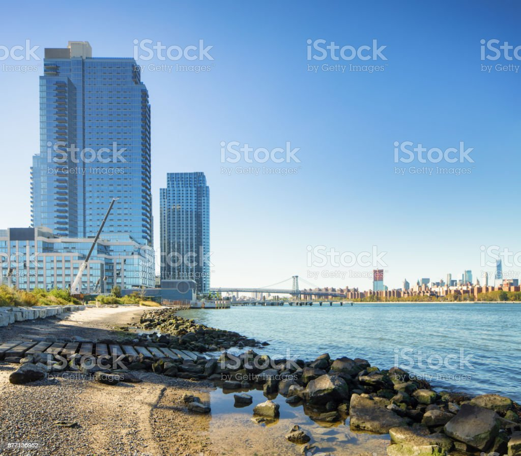 East River view towards lower Manhattan with modern apartment buildings on Brooklyn side stock photo
