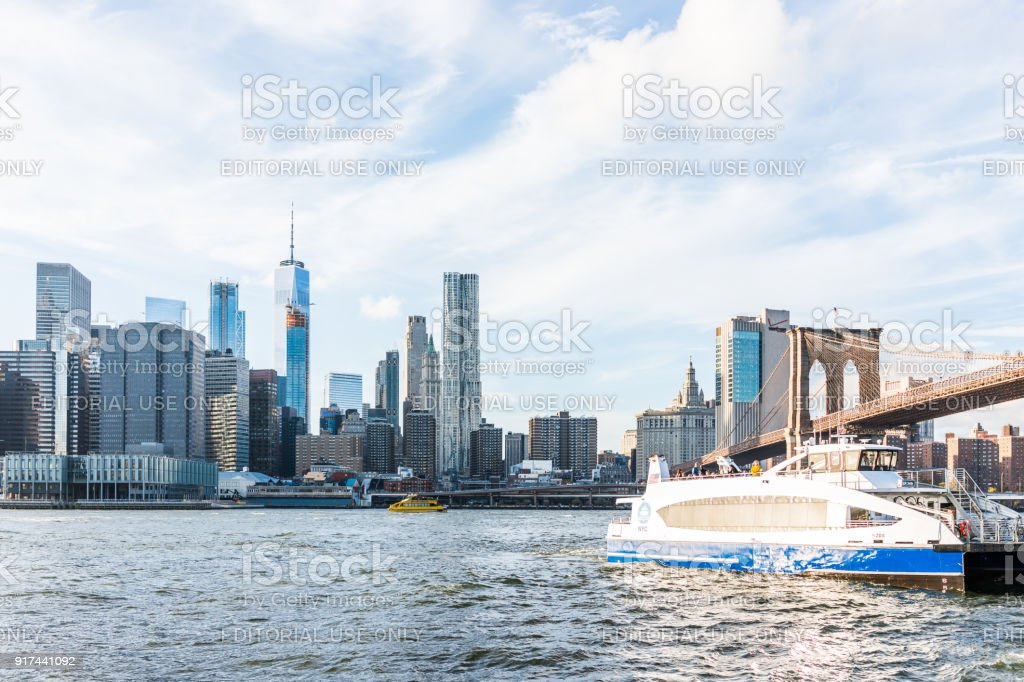 East river water with view of NYC New York City cityscape skyline, bridge, ship boat ferry swimming by lower financial downtown district skyscrapers stock photo