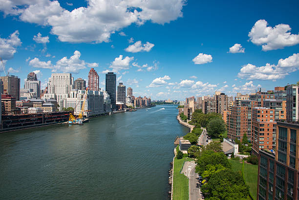 east river with roosevelt island and midtown manhattan - roosevelt island foto e immagini stock