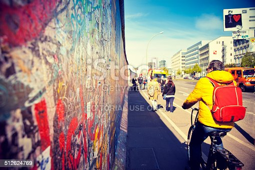 Berlin, Germany - April 17, 2014: A tourist on a bike rides along the East Side Gallery, an international memorial for freedom with paintings by artists from all over the world on one of the longest remaining sections of the Berlin Wall.