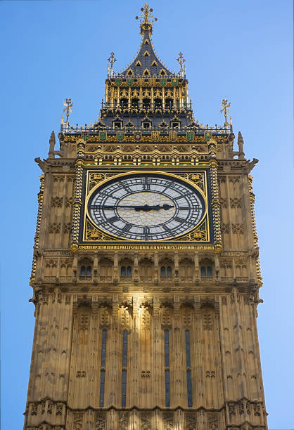 East side of famous tower clock-Big Ben with afternoon light reflection on facade and clear blue sky in background stock photo