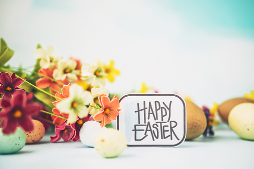 Easter arrangement with bright flowers, Easter eggs and holiday greeting