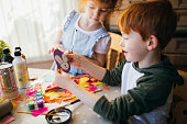Two children painting and drawing easter arts and crafts at home.