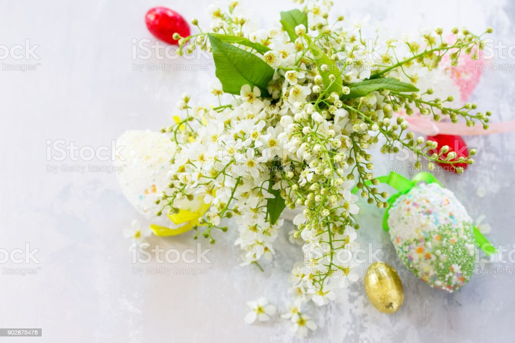 Easter background. Colorful Easter background with colored eggs and sweets on a gray stone background with copy space. stock photo