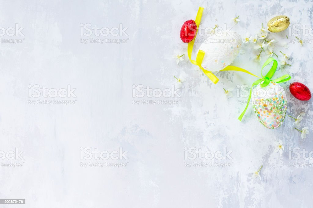 Easter background. Colorful Easter background with colored eggs and sweets on a gray stone background with copy space. Flat lay. Top view with copy space. stock photo