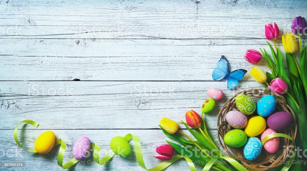 Ostern-Hintergrund. Bunter Frühling Tulpen mit Schmetterlingen und bemalten Eiern – Foto
